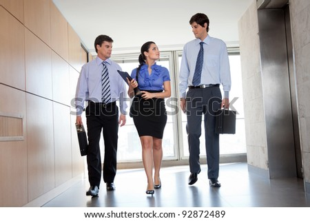 Professional businesspeople walking in office corridor