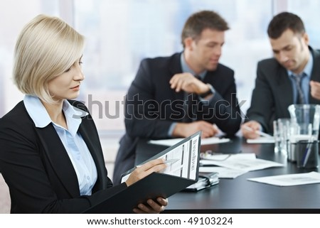 Professional businesswoman checking documents at business meeting with coworkers in background.