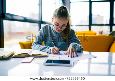 Professional businesswoman in eyeglasses concentrated on calculation of project writing report in cafe.Young clever female student doing homework task and preparing for examination in college