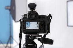 Professional camera on tripod in photo studio