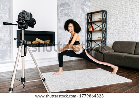 Professional camera records an African-American woman doing sports training at home, the woman is out of focus. Sports vlogging concept