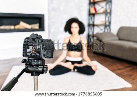 Professional camera records an African-American woman practicing yoga at home, the woman is out of focus. Sports vlogging concept, yoga coach online