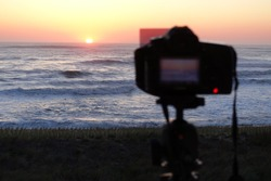 Professional camera set on a tripod with filter to capture video of a sunrise