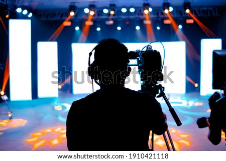 Professional cameraman - covering on event with a video, cameraman silhouette on live studio news, Selective focus Сток-фото ©