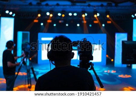 Professional cameraman - covering on event with a video, cameraman silhouette on live studio news, Selective focus