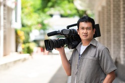 Professional cameraman using a professional camcorder outdoor filming news with blur background.