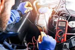 Professional car mechanic use electrician voltage multimeter, working in auto repair service.