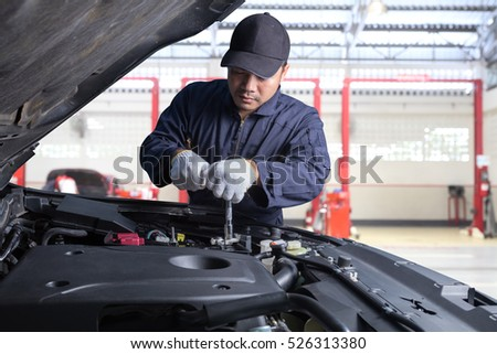 Professional car mechanic working in maintenance repair service station