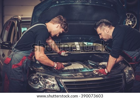 Professional car mechanics checking under hood in auto repair service. #390073603