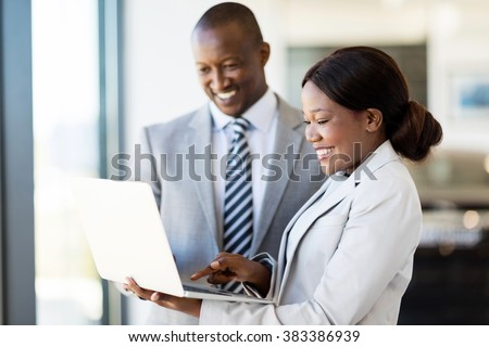 professional car sales consultants working on laptop computer inside vehicle showroom