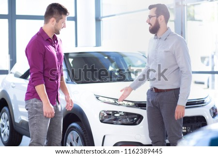 Professional car seller presenting exclusive vehicle to buyer in the showroom #1162389445