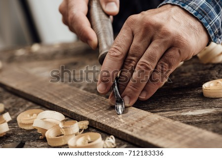 Professional carpenter at work, he is carving wood using a woodworking tool, hands close up, carpentry and craftsmanship concept