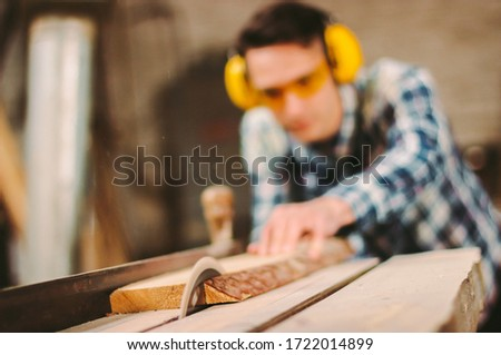 Professional carpenter using sawing machine for cutting wooden board at sawmill. Skilled cabinet maker working with electric circular saw at woodworking workshop. Man joiner, wood production workbench