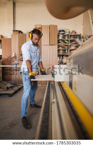 Professional carpenter wearing helmet, protective goggles and work gloves is using a wood processing machine Zdjęcia stock ©