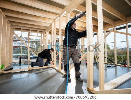 Professional Carpenters Drilling Wood At Site