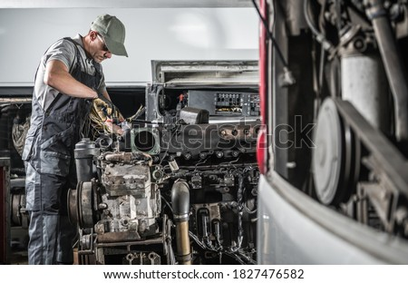 Professional Caucasian Automotive Mechanic in His 40s Repairing Powerful Heavy Duty Truck or Bus Diesel Engine Inside Truck Service Center. Transportation Industry Theme. Stock photo ©