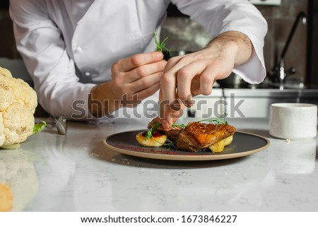 professional caucasian chef-cook decorate dish in the kitchen. man in white apron makes the finishing touch on the dish. culinary, food, restaurant, gourmet concept