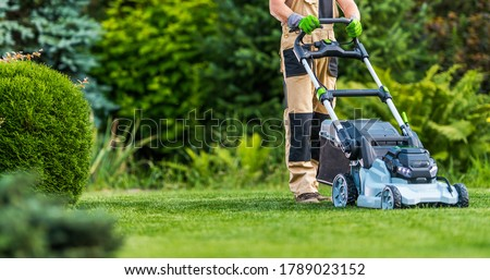 Professional Caucasian Gardener in His 40s Trimming Grass Lawn Using Modern Electric Cordless Mower. Landscaping Industry Theme.
