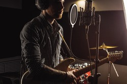 professional caucasian singer play electric guitar in recording studio. man keen on rock and roll, enjoy performing music. music, instruments concept