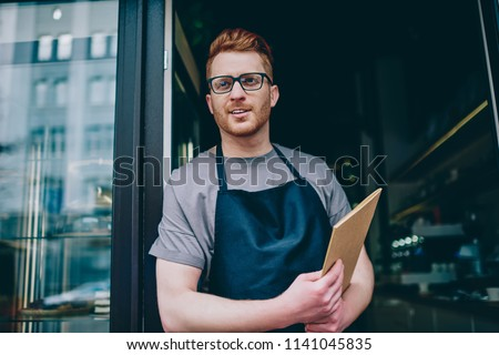 Professional caucasian waiter in black apron holding menu and smiling while inviting guests to own bakery shop.Positive male owner with red hair standing at entrance to cafeteria showing hospitality #1141045835