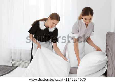 Professional chambermaids making bed in hotel room Сток-фото ©