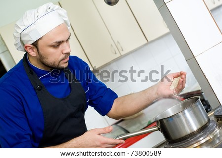 professional chef cook adding rice in pot for boiling soup in commercial kitchen