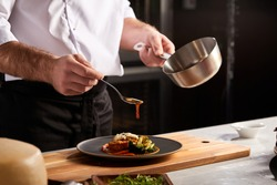 Professional Chef-cook Decorating Dish In Restaurant Kitchen Alone. Man In White Apron Makes Finishing Touch On DIsh. Culinary, Restaurant, Gourmet Concept