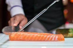 Professional chef cutting smoke salmon prepare for customer appetizer