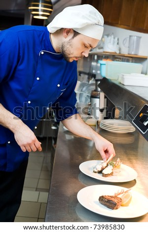 professional chef decorating prepared food on plates in commercial kitchen