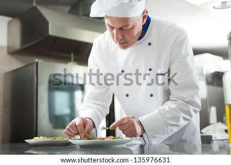 Professional chef garnishing a dish