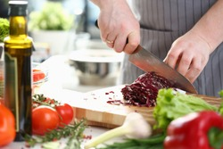Professional Chef Hands Slicing Purple Cabbage. Man Cooking Vegetable Salad. Cutting Red Cole by Sharp Knife on Wooden Board. Fresh Tom, Rosemary, Pepper, Garlic and Lettuce on Kitchen Worktop.