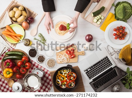 Professional chef\'s hands cooking pasta on a wooden worktop with vegetables, food ingredients and utensils, top view