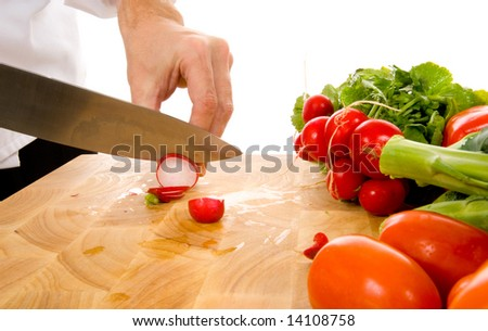 Professional chef slicing radish in front of white background