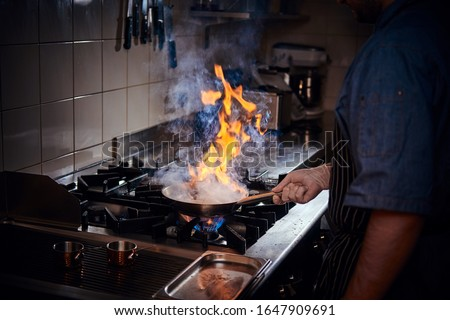 Professional chef wearing gloves and apron cooking stir-fry flambe on a pan with open fire in a dark restaurant kitchen Stock photo ©