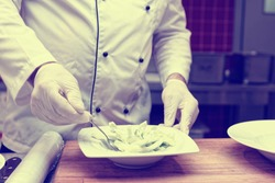 Professional chef with gloved hands is serving cucumber salad in restaurant kitchen, toned image