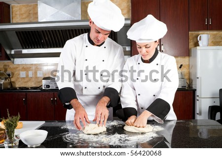 professional chefs hands kneading bread dough on a cutting board