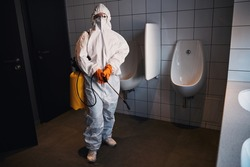 Professional cleaner in a hazmat suit standing in the public lavatory