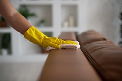 Professional cleaning service, housekeeping. Hygiene and cleanliness in the kitchen. ACleaning lady with gloves wipes dust from furniture with a cloth