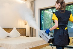 professional cleaning service. woman in uniform and gloves does the cleaning in a cottage. treatment, disinfection of the apartment with hot steam from odors and parasites, bed bugs