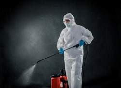 Professional cleaning staff with a To wear protective medical mask and PPE suit use chemical sprayer protect decontamination indoors. remove bacterias, viruses, and infections from the surface. COVID