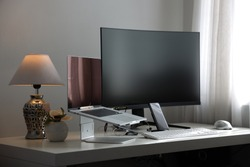professional computer workstation consisting of a laptop and a large curved monitor on a white desk