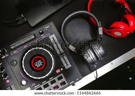 Professional concert DJ red headphones top view.High quality mixing controller for disc jockey in night club.Pro audio equipment on stage in nightclub.Play music & listen tracks with hifi headset.
