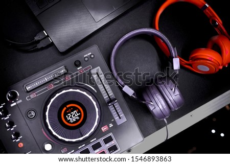 Professional concert DJ red headphones top view. High quality mixing controller for disc jockey in night club. Pro audio equipment on stage in nightclub. Play music & listen tracks with hifi headset.
