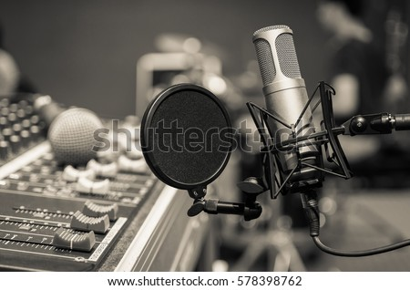 Professional condenser studio microphone over the musician blurred background and audio mixer, Musical instrument Concept.