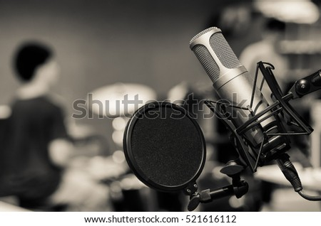 Professional condenser studio microphone over the musician blurred background, Musical instrument Concept