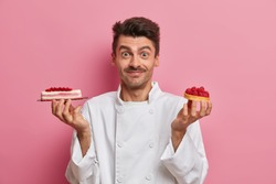 Professional confectioner works in pastry shop, holds yummy handmade cakes, poses in restaurant kitchen, wears white uniform, cooks delicious sweet dessert, isolated on pink background. Bakery concept