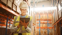 Professional Confident Worker Wearing Hard Hat Checks Stock and Inventory with Digital Tablet Computer in the Retail Warehouse full of Shelves with Goods. Working in Logistics, Distribution Center