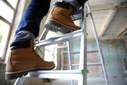 Professional constructor on ladder in old building, closeup