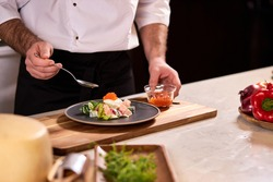 professional cook adds red caviar for salad, making tasty food in restaurant, master class of cooking. close-up photo