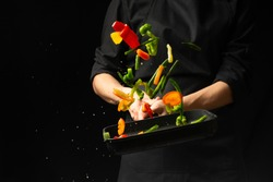 Professional cook. He prepares a dish with vegetables in a saucepan. on black background, menu, recipe book, healthy food